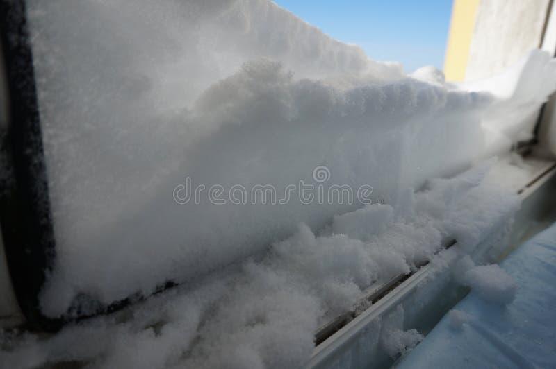 śnieg na windowsill przeciw niebieskiemu niebu zdjęcie stock