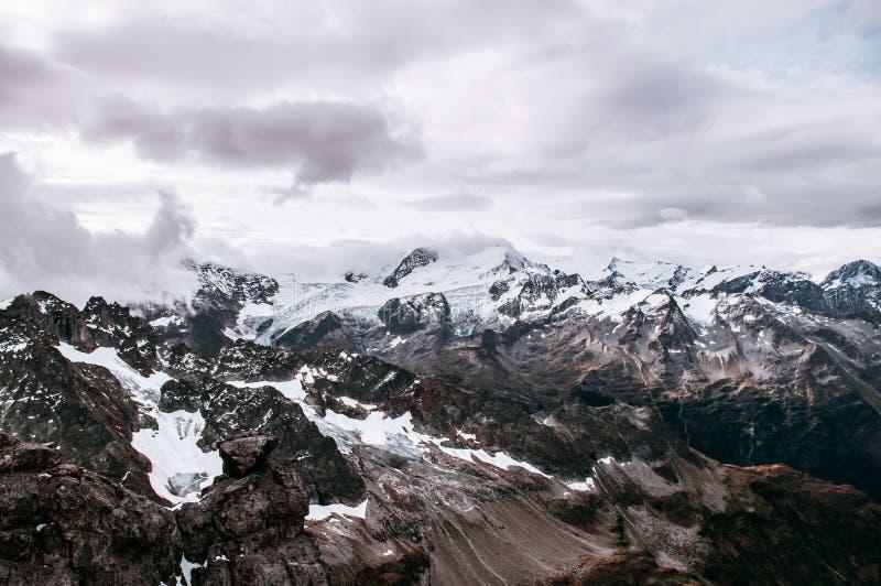 Śnieg rockowa faleza za obłoczną i Halną doliną Titlis w Engelberg, Szwajcaria obrazy stock