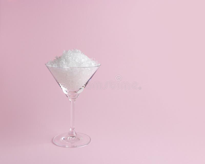 Śnieg w Martini szkle na pastelowych menchii tle Minimalny bo?ych narodze? lub nowego roku poj?cie obraz stock
