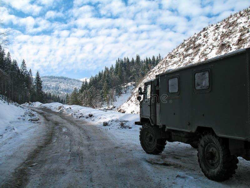 Śnieg zakrywał halną drogę w zimie z ciężarówką zdjęcia royalty free