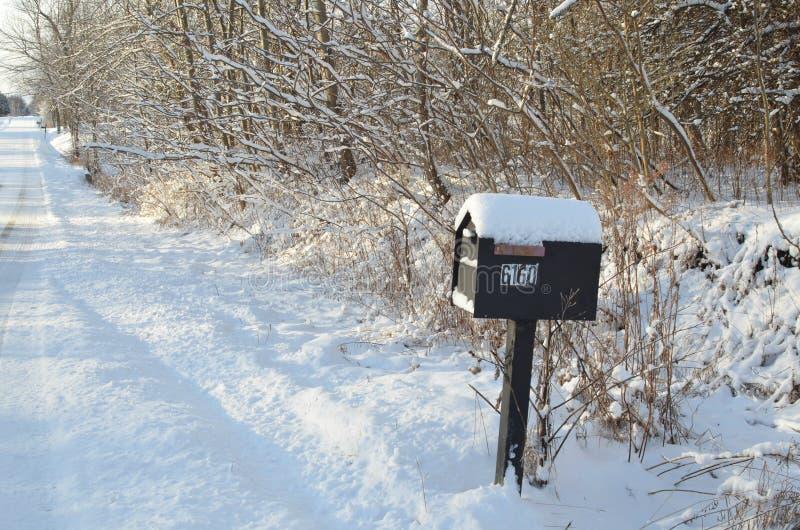 Śnieg zakrywająca skrzynka pocztowa śnieżnego ranku wiejska droga zdjęcie stock