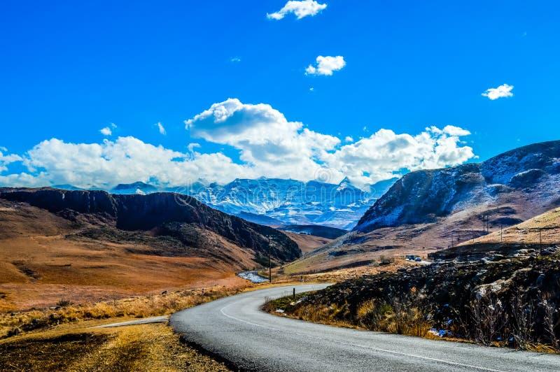 Śniegu krajobraz w Drakensberg górach w Underberg Południowa Afryka pod niebieskim niebem i flakey chmurami obrazy royalty free