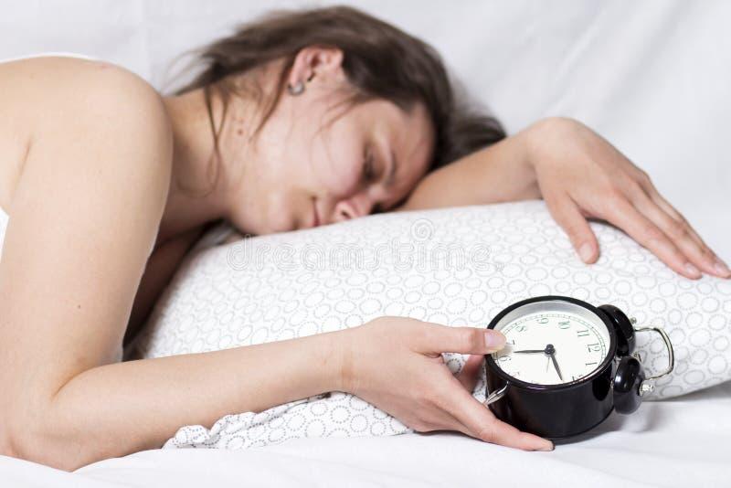 Śpiąca dziewczyna no może budził się od dzwonu alarmowego Kobieta śpi w łóżku i trzyma budzika w jej ręce fotografia royalty free