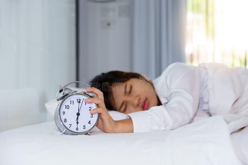 Śpiąca młodej kobiety rozciągania ręka próbować zwłoka budzika wewnątrz obrazy royalty free