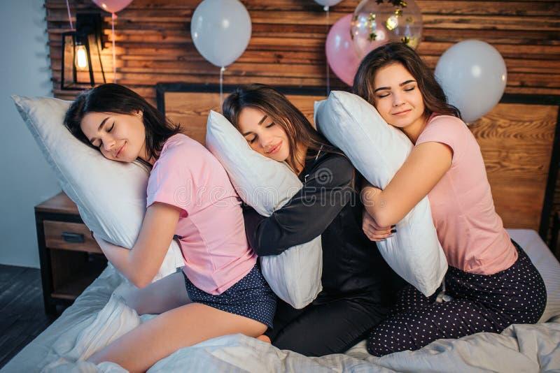 Śpiące młode kobiety siedzi na łóżku w pokoju Ich kierowniczy lying on the beach na poduszkach w rękach Śpią Modela uśmiech fotografia royalty free