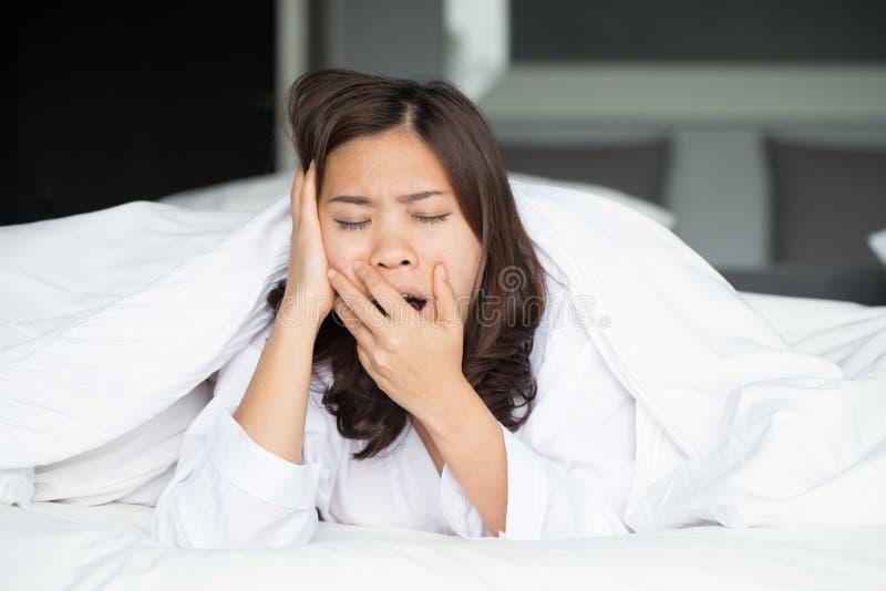 Śpiący azjatykci kobiety ziewanie w łóżku zdjęcia stock