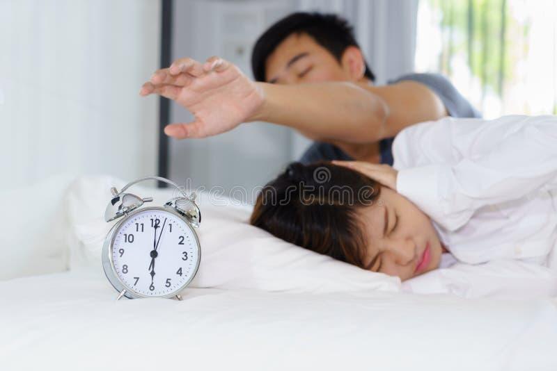 Śpiący mężczyzna próbować obraca daleko budzika obok kobiety dokuczającej obok obrazy stock