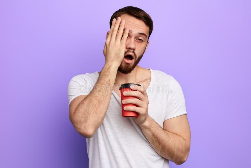 Śpiący przystojny mężczyzna pije kawę z palmą na jego policzku fotografia stock