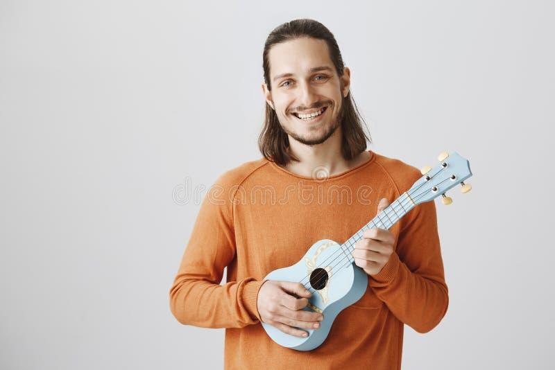 Śpiewacka piosenka podczas podróży w pociągu Portret życzliwa przystojna samiec w pomarańczowym puloweru mienia ukulele, bawić si fotografia royalty free