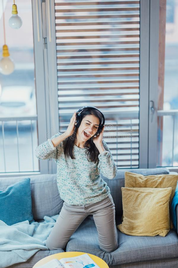 Śpiewacka piosenka z emocją Ćwiczy wokalnie zdolność Udoskonalający pasmo Rozochocona kobieta słucha muzyka z wielkimi hełmofonam obrazy stock