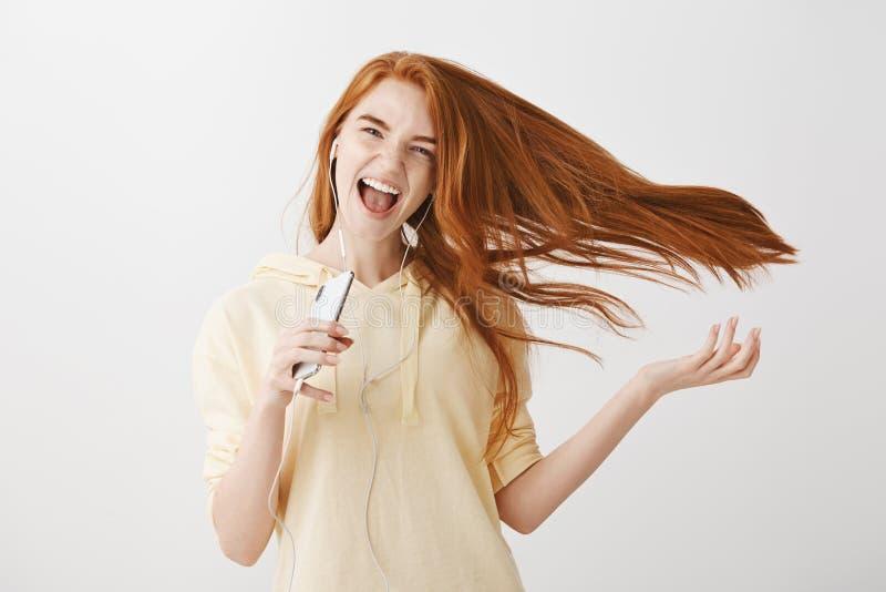 Śpiewający ona serce out Portret trzyma chłodno ufna budzący emocje młoda kobieta z imbirowym włosy który macha na powietrzu, obraz royalty free