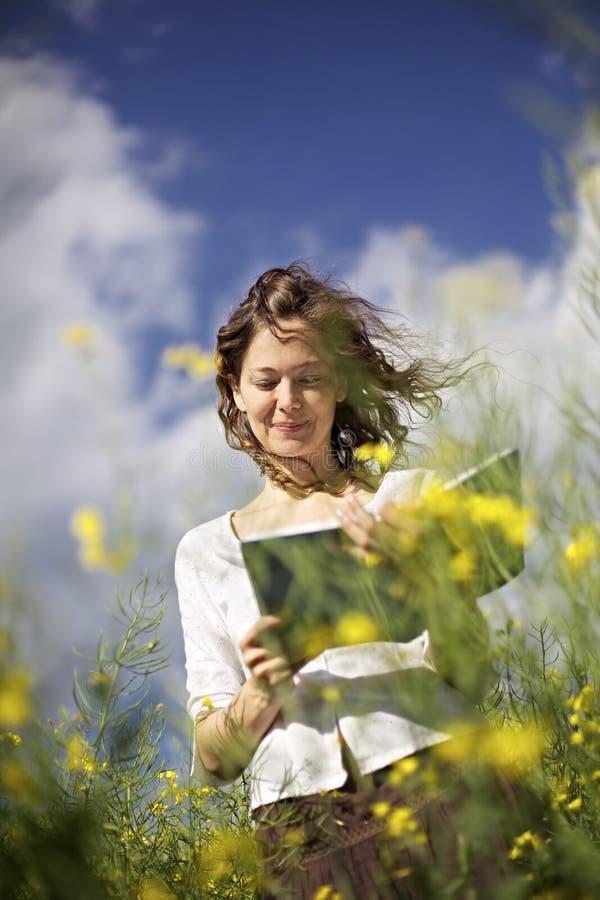 śródpolnego rapeseed czytelnicza kobieta zdjęcie stock