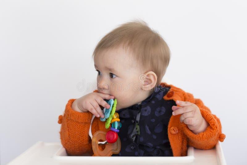 ?redni horyzontalny strza? uroczy uczciwy berbe? dziewczyny obsiadanie w wysokim krze?le trzyma colourful zabawk? jej usta w po?? zdjęcia stock