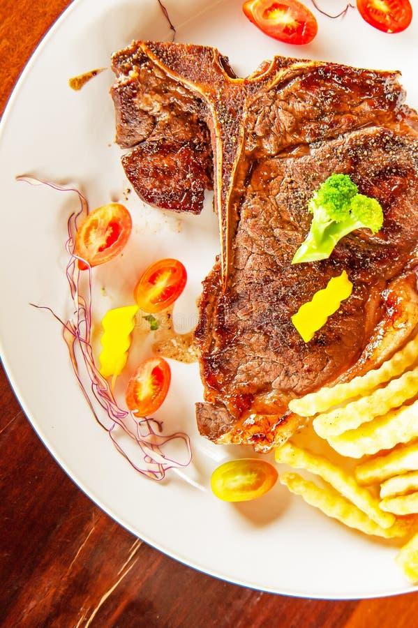Średni rzadki Piec na grillu kość stek słuzyć na bielu talerzu obrazy stock