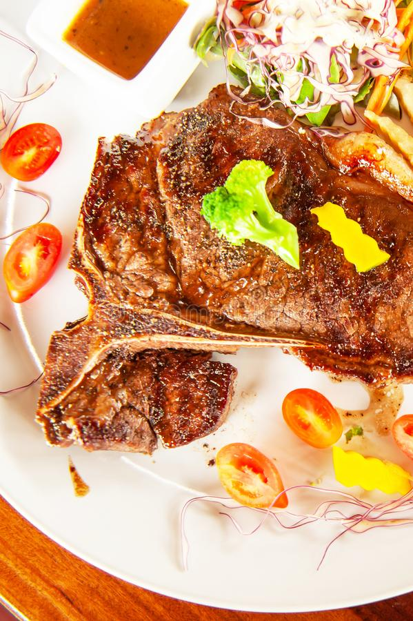 Średni rzadki Piec na grillu kość stek słuzyć na bielu talerzu fotografia stock
