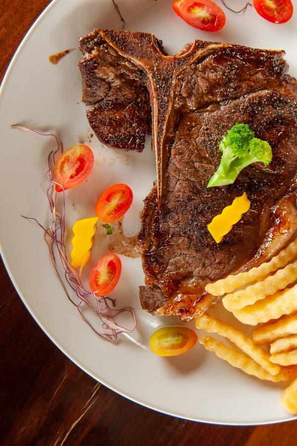 Średni rzadki Piec na grillu kość stek z dłoniakami, sałatką i pomidorami na słuzyć bielu talerzu na drewnianym stole francuza, O zdjęcie stock