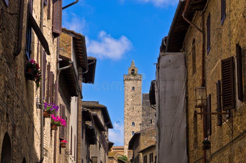 Średniowieczna architektura San Gimignano, góruje i domy dekorujący z kwiatami, Tuscany zdjęcia stock