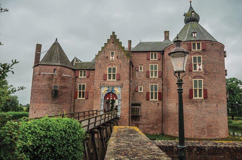 Średniowieczny Ammersoyen kasztel z swój cegłą góruje, drewniany most i zieleń ogród na chmurnym dniu obrazy royalty free
