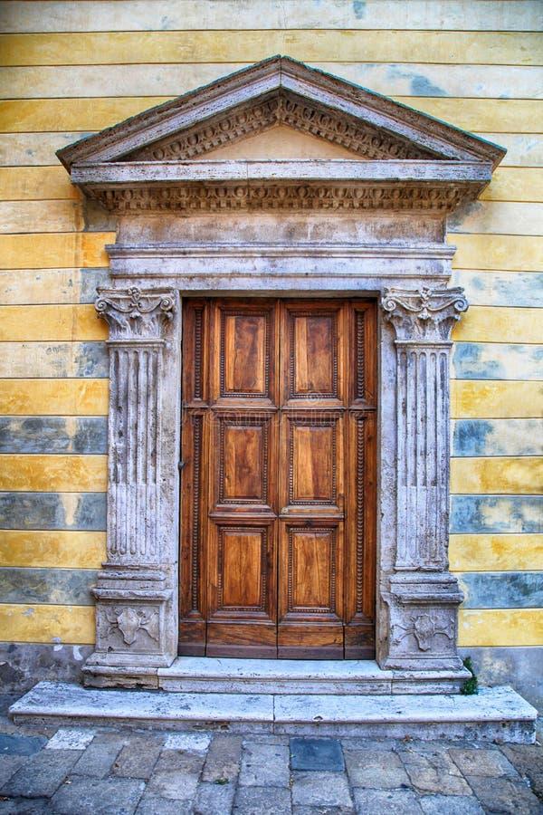 Średniowieczny antyczny drewniany drzwi z ozdobnymi kamiennymi kolumnami, Włochy obrazy royalty free