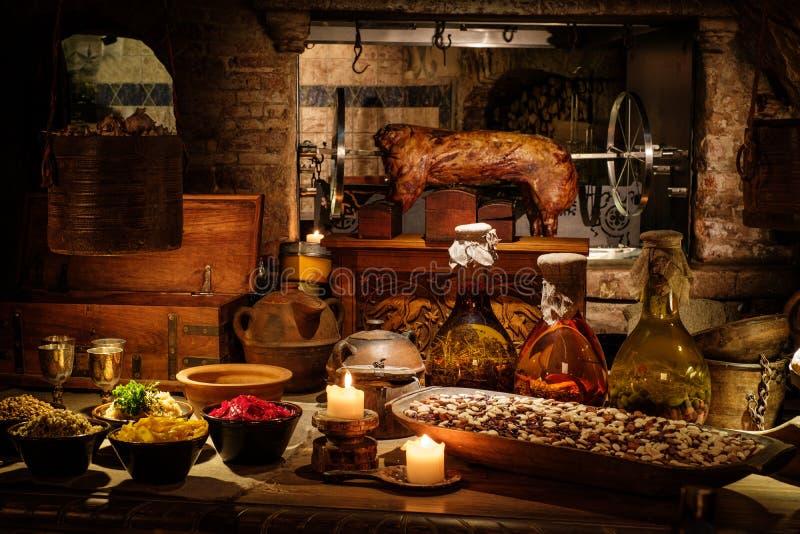 Średniowieczny antyczny kuchenny tabe z typowym jedzeniem w królewskim kasztelu zdjęcia royalty free