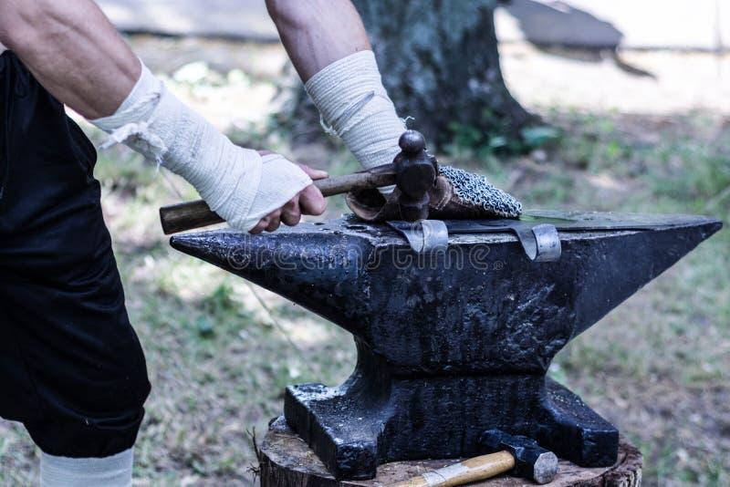 Średniowieczny blacksmith wręcza ręcznie skucie metal dla ax broni z młota narzędziem na czarnym kowadle obrazy stock