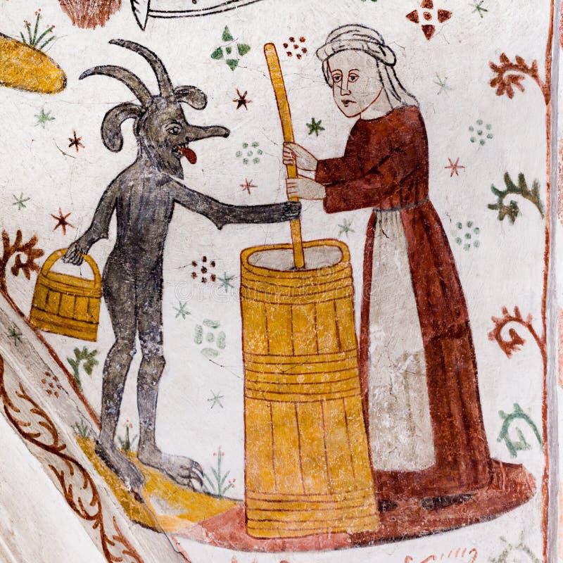 Średniowieczny fresk kobieta roi się masło z diabłem zdjęcie stock