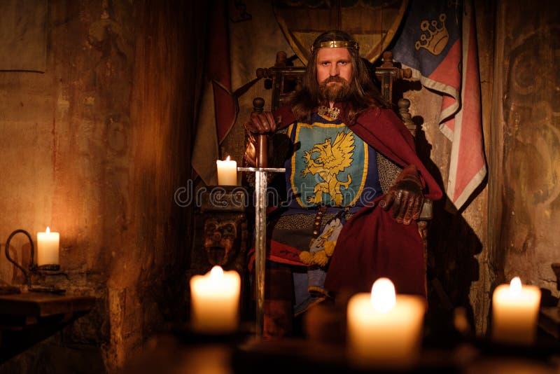 Średniowieczny królewiątko na tronie w antycznym grodowym wnętrzu zdjęcia stock