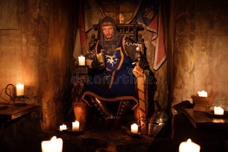 Średniowieczny królewiątko na tronie w antycznym grodowym wnętrzu obrazy royalty free