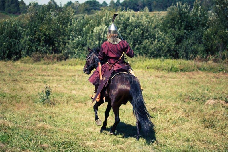 Średniowieczny opancerzony rycerz na koniu od fantazji Equestrian żołnierz w dziejowym kostiumu jest w lata polu zdjęcia royalty free