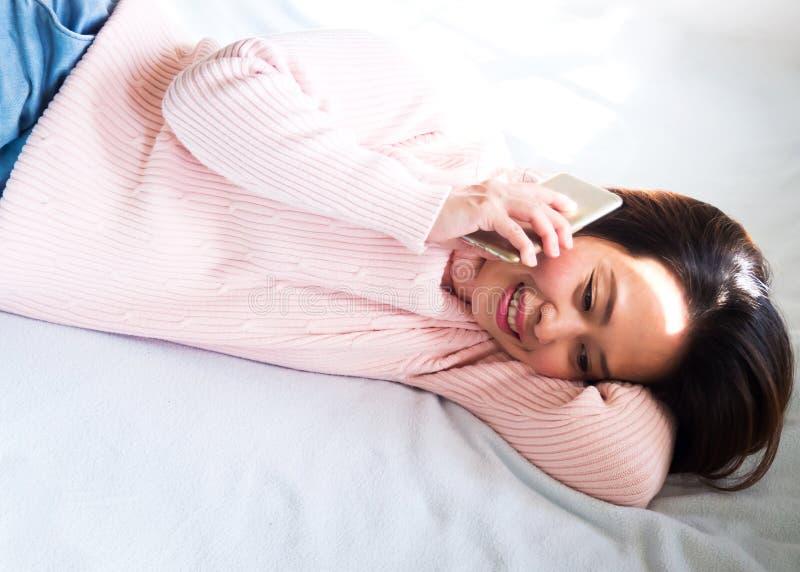 Środkowa dorosła Azjatycka kobieta kłaść w dół na łóżku i używa mobilnego pho zdjęcie stock