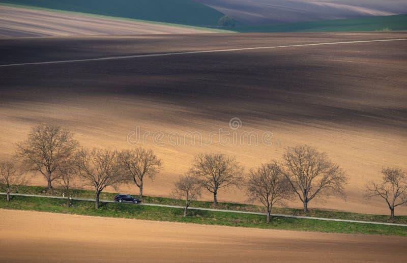 Środkowy Europa Czarny samochód jedzie wśród stubarwnego górkowatego pola Krajobraz z błyszczącym czarnym samochodem, barwiący za zdjęcie royalty free