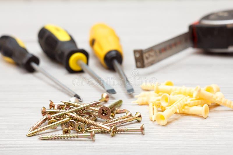 Śrubokręty, taśmy miara i śruby na białym drewnianym tle, fotografia stock