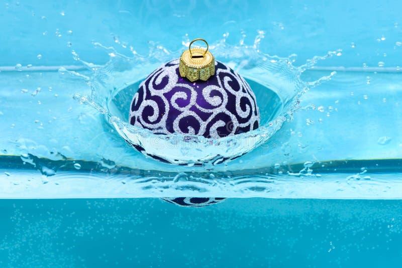Świąteczna dekoracja dla choinki, fiołkowa piłka opuszczał w wodę z pluśnięciami, błękitny tło Boże Narodzenia zdjęcia stock