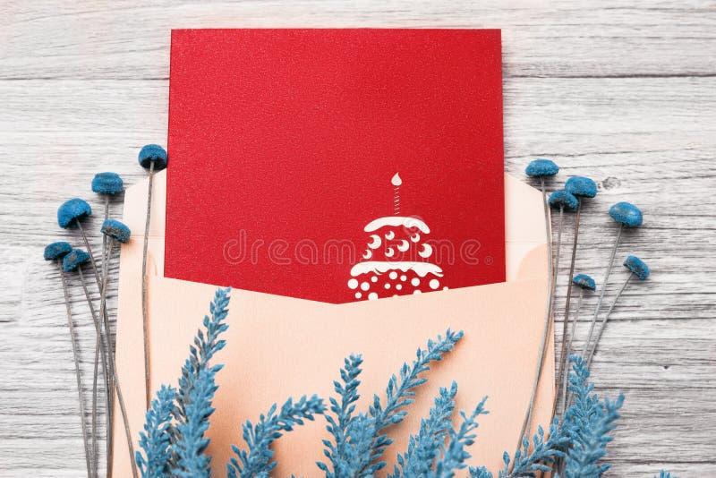 Świąteczna pocztówka w kopercie i kwiatach na drewnianym tle obraz stock