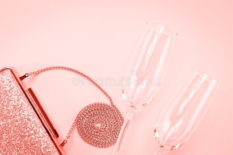 Świątecznego wieczór złoty sprzęgło i dwa szampańskiego szkła na menchiach Wakacje i świętowania tło Luksusowi akcesoria i przyję fotografia royalty free