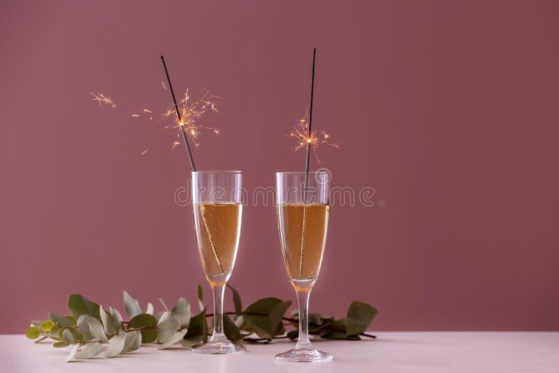 Świąteczni Bożenarodzeniowi sparklers w szkłach z szampanem na stole przeciw koloru tłu obrazy stock