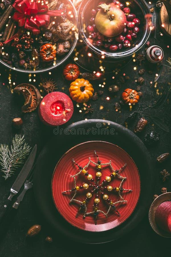 Świąteczny boże narodzenie stół z czerwień talerzami dekorującymi z płatek śniegu, jedlinowymi gałąź, płonącymi świeczkami, wysus fotografia royalty free