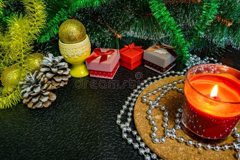 Świąteczny Bożenarodzeniowy skład z wosk świeczkami, prezentów pudełkami i srebnymi koralikami, Dekoracje dla sylwesteru Na ciemn obrazy stock