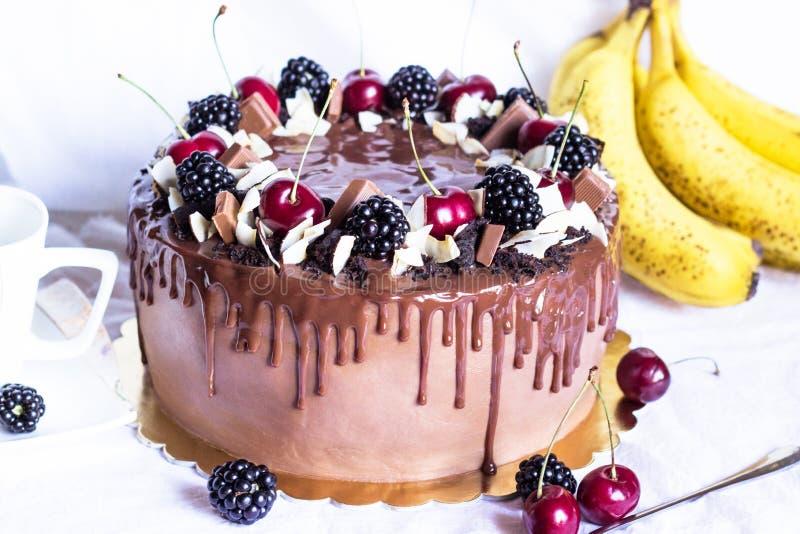 Świąteczny czekoladowy tort z jeżynową i słodką wiśnią na białym tle Boczny widok fotografia royalty free