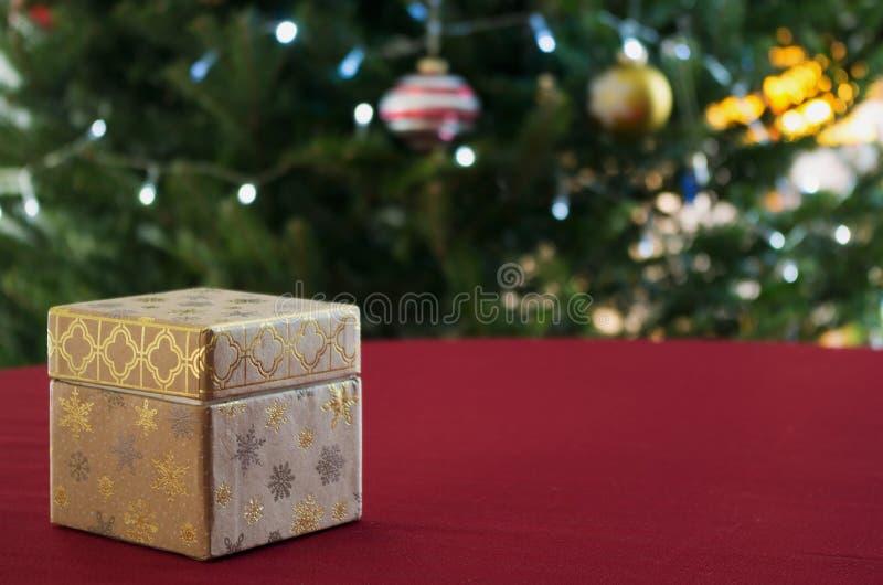 Świąteczny stół z prezenta pudełkiem i Dekorującą choinką w tle zdjęcia stock