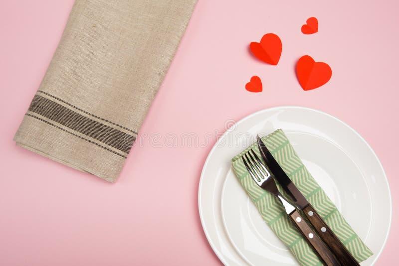Świąteczny stołowy położenie dla walentynka dnia z rozwidleniem, nóż, serca na czerwonym tle Odgórny widok - Wizerunek obraz royalty free