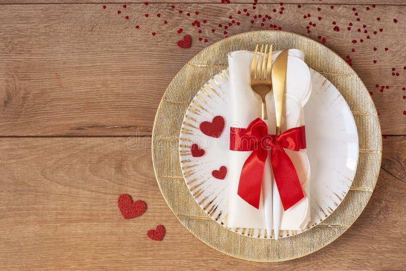 Świąteczny stołowy położenie dla walentynka dnia z rozwidleniem, nożem, czerwonym łękiem i sercami na drewnianym stole, Przestrze fotografia royalty free