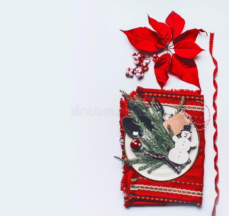 Świątecznych bożych narodzeń stołowy położenie z czerwoną pieluchą, cutlery, talerzem, jedlinowymi śniadanio-lunch, bałwanem, wys obraz royalty free