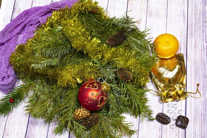 święta bożego życie wciąż gałąź zielona świerczyna z ornamentami, torbą złoto, tangerine i cukierkiem na lekkim drzewnym tle, obrazy stock