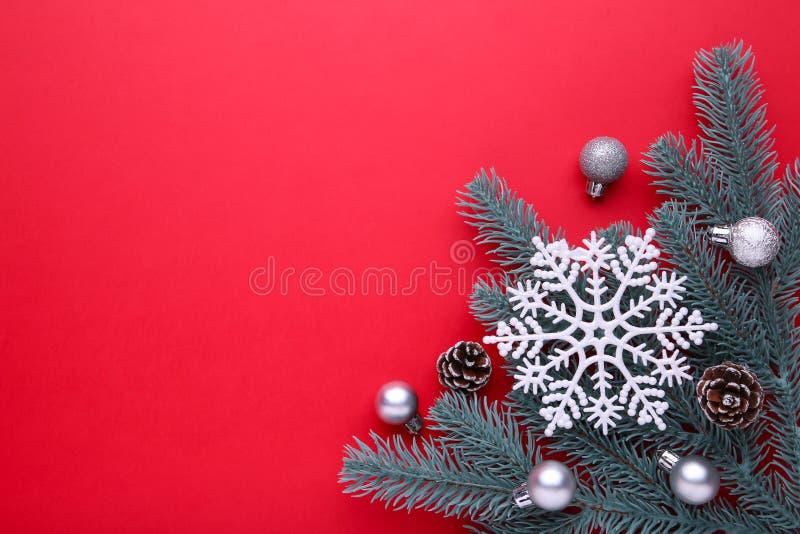 Święta dekorują odznaczenie domowych świeżych pomysłów Jedliny gałąź z piłkami, garbki, płatek śniegu na czerwonym tle zdjęcie royalty free