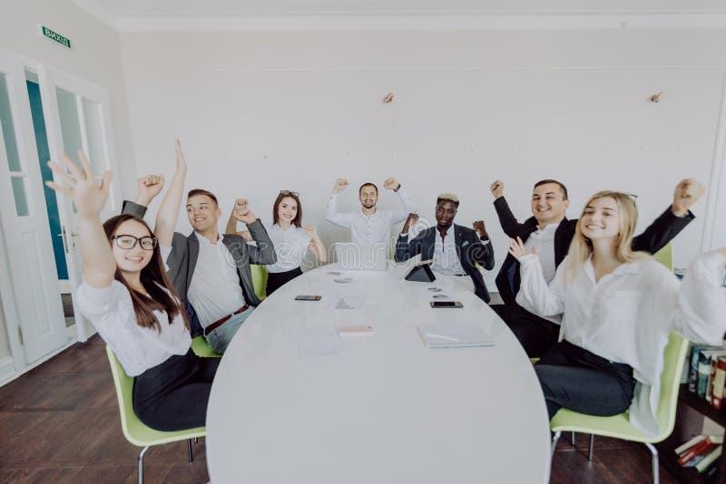 świętowaniu sukcesu Grupa młodzi ludzie biznesu podnosi ich ręki i patrzeje szczęśliwy podczas gdy siedzący wokoło biurka wpólnie zdjęcia stock