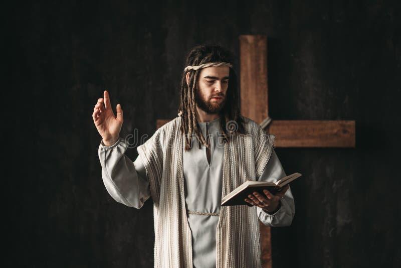 Święty jezus chrystus modlenie z biblijnym w rękach obraz stock