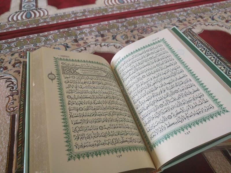 Święty koran w Angielskim i Arabskim na pięknym wzorze Projektował dywanika zdjęcia stock