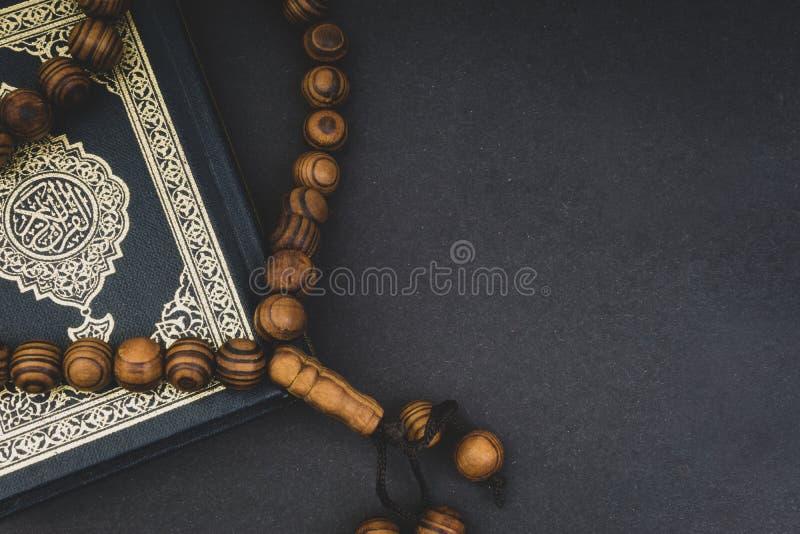 Święty koran z tasbih lub różana koralikami nad czarnym tłem obraz royalty free