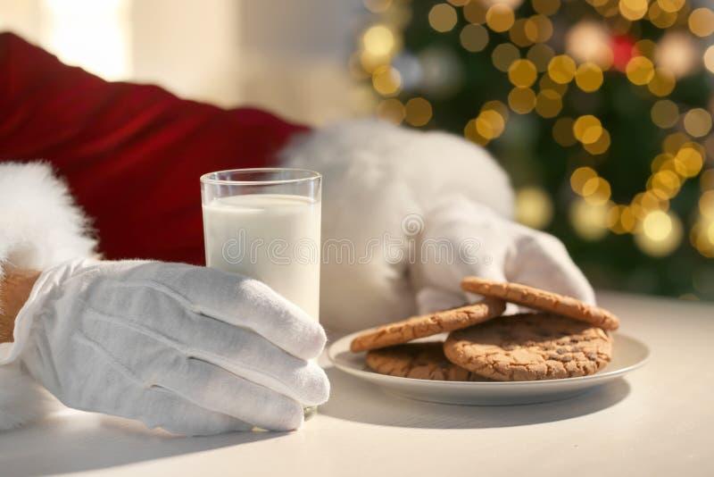 Święty Mikołaj łasowania ciastka i pić przy stołem mleko, zbliżenie obraz royalty free